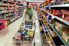 Il cliente passa in rassegna la navata laterale del supermercato Fotografie Stock Libere da Diritti