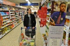Il cliente passa in rassegna una navata laterale del supermercato Fotografia Stock