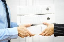 Il cliente sta passando la documentazione nei raccoglitori al suo partner immagine stock libera da diritti
