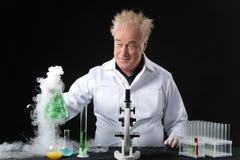 Il clinico pazzo studia in boccetta della tenuta e del laboratorio Immagine Stock