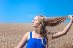 Il closing della ragazza osserva sul giacimento di grano e del cielo blu Immagine Stock Libera da Diritti
