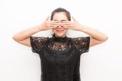 Il closing sorridente della donna dell'Asia osserva con le sue mani sul backgrou bianco Immagine Stock