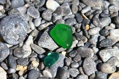 Il coccio di vetro sveglio lucidato dal mare sulle pietre scure della spiaggia - pietre nere del ciottolo sulla spiaggia Foto del immagine stock libera da diritti
