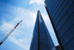 Il coccio più una gru e un altro edificio per uffici vetroso Fotografia Stock Libera da Diritti