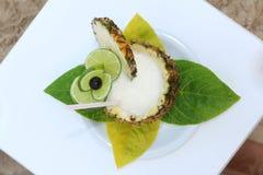 Il cocktail è servito in un ananas sulla spiaggia Fotografie Stock Libere da Diritti