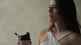 Il cocktail attraente della proteina delle bevande della donna è in appartamento stock footage
