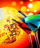Il cocktail blu e rosso con il fondo scintillante della palla della discoteca con spazio per testo ha selezionato il fuoco Immagini Stock Libere da Diritti