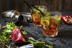 Il cocktail di rinfresco di mojito con granato, la menta e la calce, su una tavola di pietra grigio scuro con l'agitatore per la  fotografie stock