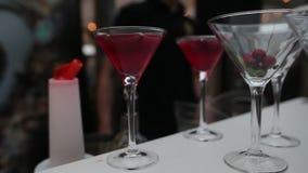 Il cocktail di versamento nella fucilazione di vetro del primo piano di martini guida intorno video d archivio