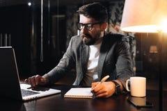 Il collega barbuto si siede dalla tavola di legno con la lampada e per mezzo del taccuino contemporaneo Penna della tenuta dell'u immagine stock