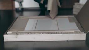 Il collettore della mobilia apre la scatola ed elimina la carta da imballaggio archivi video