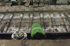 Il collettore di immondizia delle ferrovie indiane riunisce l'immondizia dalla ferrovia fotografie stock