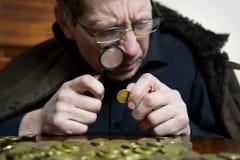 Il collettore esamina la sua ricchezza con le candele accese Fotografia Stock Libera da Diritti