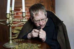 Il collettore esamina la sua ricchezza con le candele accese Fotografie Stock Libere da Diritti