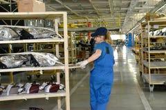 Il collettore femminile trasporta uno scaffale con il faro dell'automobile Fotografie Stock