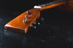 Il collo della chitarra sul nero Immagine Stock