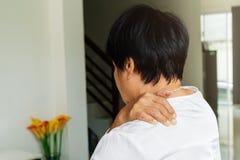 Il collo e la spalla fanno soffrire, donna anziana che soffrono dal collo e ferita sulla spalla, concetto di problema sanitario fotografia stock