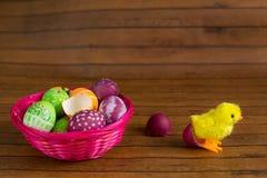 Il colore di Pasqua ha dipinto le uova merce nel carrello ed il pulcino del giocattolo Fotografia Stock