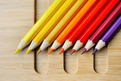Il colore disegna a matita lo spettro su fondo di legno Fotografia Stock