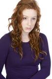 Il colore rosso ha diretto sembrare teenager triste contro bianco Fotografia Stock