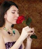 Il colore rosso sentente l'odore della ragazza graziosa è aumentato Immagini Stock Libere da Diritti