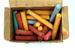 Il colore segna il bastone col gesso in vecchia scatola di carta isolata su fondo bianco immagini stock libere da diritti