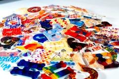 Il colore segna la plastica con lettere su fondo bianco Fotografia Stock