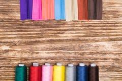 Il colore si arrotola con i fili e le chiusure lampo luminose su un fondo di legno Immagini Stock Libere da Diritti