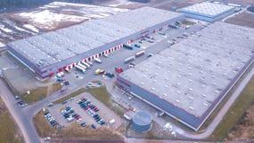 Il colpo aereo del magazzino industriale del magazzino in cui molti trasportano con i rimorchi dei semi carica le mercanzie aereo fotografia stock