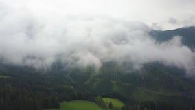 Il colpo aereo in nuvole, macchina fotografica ? sopra le montagne ed i campi verdi video d archivio