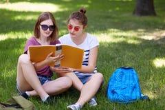 Il colpo all'aperto delle studentesse graziose indossa gli occhiali da sole alla moda, si siede le gambe attraversate su erba ver Immagini Stock