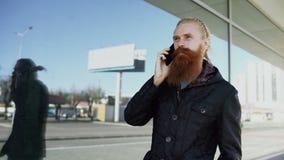 Il colpo del carrello di giovane uomo barbuto dei pantaloni a vita bassa ha concentrato la conversazione sul telefono su citystre video d archivio