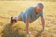 Il colpo del maschio maturo spinge aumenta su erba verde, essendo flessibile, si scalda prima di pareggiare, gode dell'aria fresc Immagini Stock Libere da Diritti