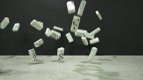 Il colpo del movimento lento dei domino bianchi cade su un fondo nero stock footage