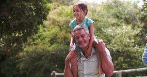 Il colpo del movimento lento dei padri che danno i bambini trasporta sulle spalle i giri stock footage