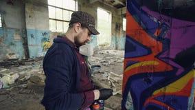 Il colpo del primo piano dell'interno di lavoro dell'uomo del pittore barbuto bello dei graffiti adandoned la costruzione facendo archivi video