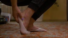 Il colpo del primo piano della donna che sfrega il piede irritato ha storto il dolore della caviglia stock footage