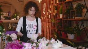 Il colpo del primo piano delle rose fresche di colore bianco con i gambi e le foglie verdi ha sistemato nei mazzi da vendere in n stock footage