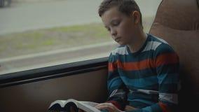 Il colpo del primo piano di giovane scolaro che attraversa in bus through la città e legge un libro stock footage