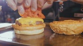 Il colpo del primo piano del ` s del cuoco unico passa la preparazione dell'hamburger con la crocchetta ed il formaggio del manzo immagine stock