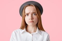 Il colpo dello studio di sembrare piacevole femminile con lo sguardo di ribaltamento, porta il cappello elegante, labbra delle cu Fotografie Stock