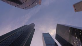 Il colpo di angolo basso della macchina fotografica che gira davanti a moderno, grattacieli ha fatto di vetro stock footage