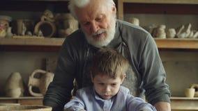 Il colpo di inclinazione-su del ragazzino concentrato che fa l'argilla dipende la ruota di lancio mentre il suo scultore esperto  archivi video