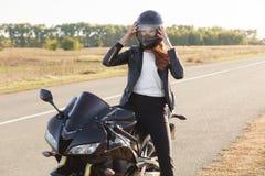 Il colpo esterno del motociclista femminile veloce indossa il casco protettivo, posa sulla motocicletta, supporti sulla motocicle immagine stock libera da diritti