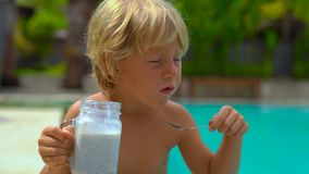Il colpo lento del ragazzino mangia un budino di chia che si siede da un lato di uno stagno video d archivio