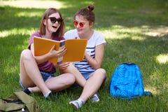 Il colpo orizzontale degli studens femminili felici ritiene rilassato mentre sieda le gambe attraversate su erba verde, godono de Fotografia Stock