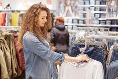 Il colpo orizzontale della femmina piacevole fa l'acquisto, esamina la varietà di vestiti sui ganci, visita il negozio di modo, e Fotografie Stock Libere da Diritti