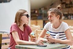 Il colpo orizzontale delle femmine amichevoli si incontra insieme in caffè, mangia il gelato ed ha espressioni positive, gode del Fotografia Stock