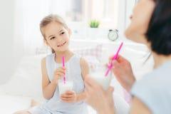 Il colpo potato di bello piccolo bambino femminile beve il frappè saporito insieme a sua madre, gode del buongiorno e della calma fotografia stock libera da diritti