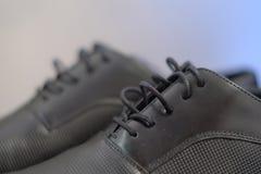 Il colpo potato primo piano delle scarpe di cuoio maschii nere utilizzate, lucidi eleganti delle calzature e aspetta per essere i fotografia stock